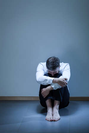 lonliness: Portrait of depressed young businessman sitting on the floor Stock Photo