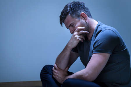 sorrowful: Portrait of sorrowful, grieving man sitting on the floor