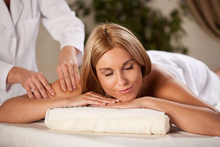 Young woman relaxing during pleasant arm massage photo