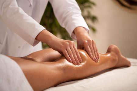 piernas: Vista horizontal de la masajista que da masajes a la pantorrilla femenina