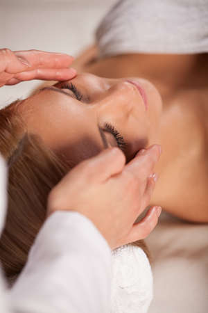 Close-up of woman relaxing during face massage photo