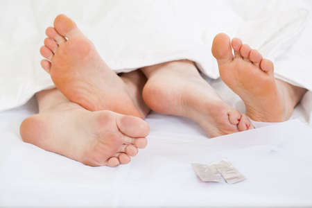 sex on bed: Close up of feet of a happy couple in bed