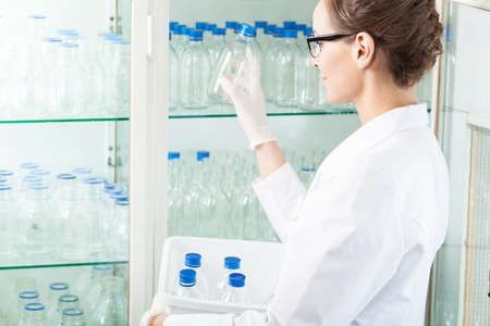 clean room: Worker of laboratory putting empty bottle into case Stock Photo