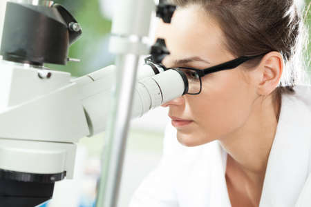 research worker: Female scientist looking through microscope in laboratory