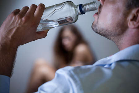 alcoholismo: Hombres borrachos con botella y su esposa asustada