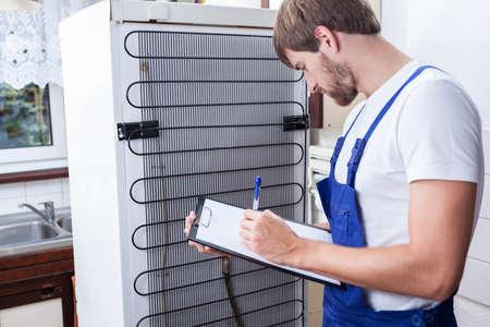 Horizontal view of handyman during fridge repair Stock Photo