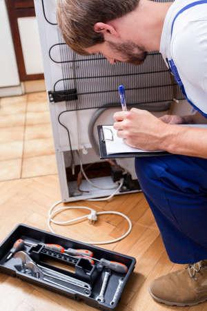 industrious: View of man working with broken fridge