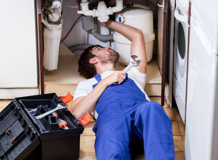 industrious: Man repairing pipes in the kitchen sink