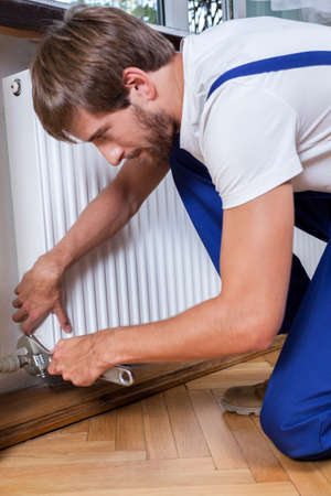 industrious: Vertical view of fixing radiator at home Stock Photo