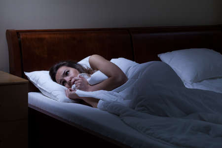 fear woman: Terrified woman lying in bed at night Stock Photo