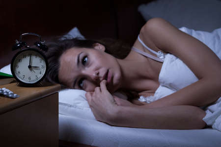 Woman lying in bed sleepless at night photo