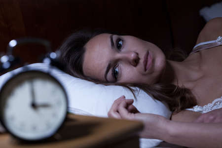 headache: Woman lying in bed suffering from insomnia Stock Photo