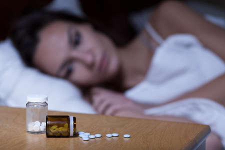 Woman lying in bed, taking sleeping pills