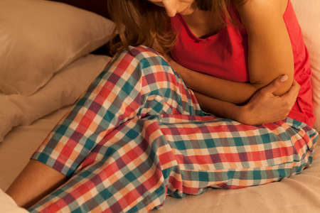 Young woman in bed suffering from abdominal pain photo