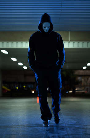 a situation alone: View of mugger wearing mask at night Stock Photo