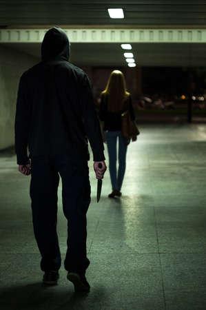 女の人の後ろにナイフで危険な男 写真素材