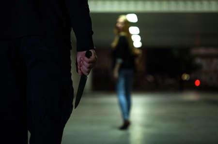 Hombre peligroso con el cuchillo y el potencial víctima Foto de archivo - 32559411