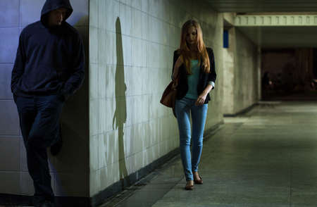 threats: View of lonely woman walking at night Stock Photo