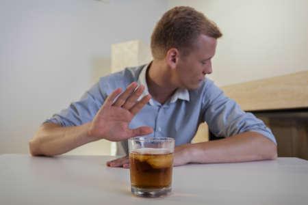 no pase: El joven se niega a beber un vaso de whisky