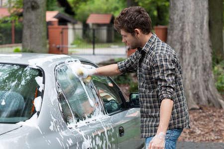 car polish: Young tall man washing his silver car Stock Photo