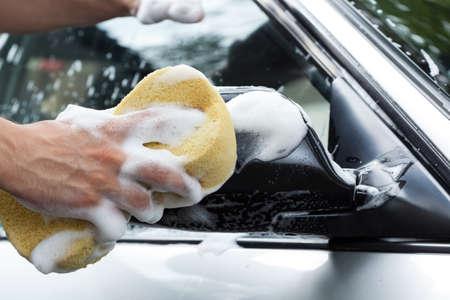 Mans hand holding sponge full of foam photo