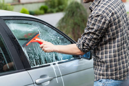 moisten: Young tall man cleaning the window in his new silver car