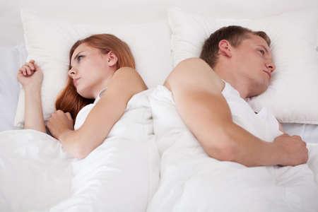 couple au lit: Couple couché dans le lit dos à dos