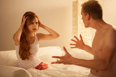 wives: Horizontal view of married couple arguing in bed