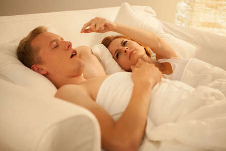 Angry woman and her snoring husband lying in bed Stock Photo