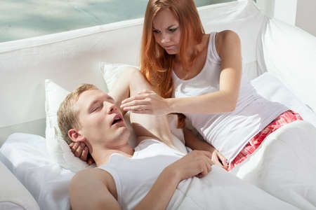 snoring: Image of woman irritated by snoring husband
