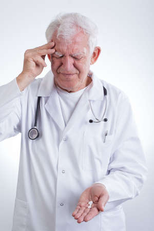 painkillers: Experienced physician having headache and taking painkillers