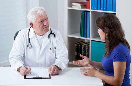 practiced: Practiced doctor talking with young female patient Stock Photo