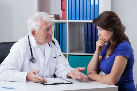 practiced: Senior male doctor talking with worried patient Stock Photo