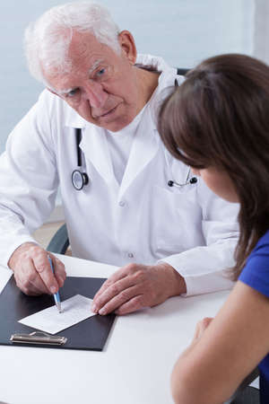 Image of experienced physician giving patient prescription photo