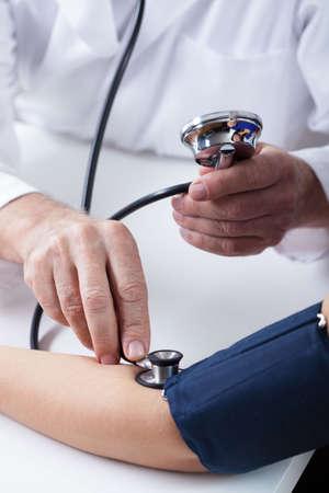 Close-up of doctors hands measuring blood pressure Фото со стока