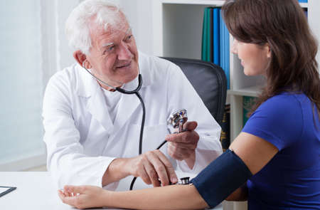 general practitioner: General practitioner taking blood pressure of young woman Stock Photo