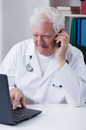 practiced: Modern senior doctor using phone and laptop