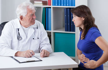 Giovane donna con stomachache visita medico anziano