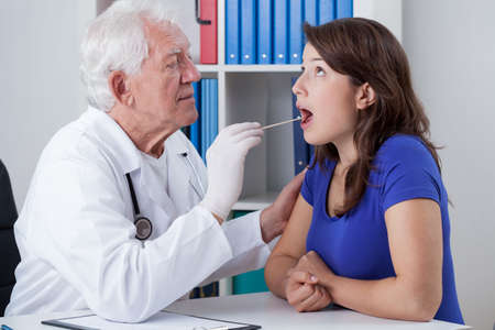 pharyngitis: General practitioner examining throat of young woman