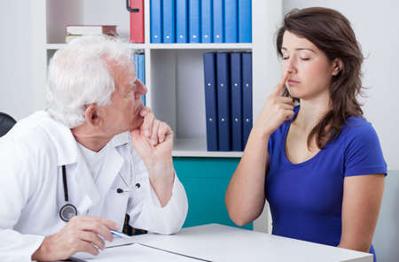 diagnosing: Male physician diagnosing patient with neurological problems