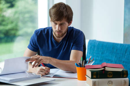 study: Young student learning and spending time behind the desk