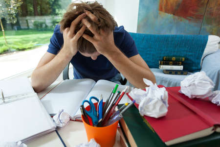frustrated student: Exhausted student in blue t-shirt learning at home Stock Photo