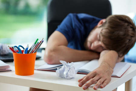 Tired student fall asleep during preparation to exams photo