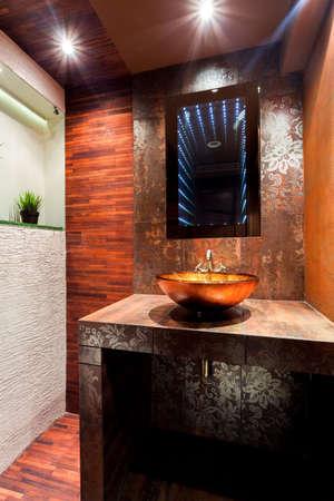 handbasin: Interior of luxury modern brown and orange bathroom Stock Photo