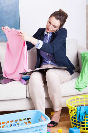 working from home: Young mother working from home and folding clothes Stock Photo