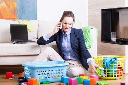 Young woman cleaning up toys and working from home