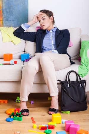 habitacion desordenada: Madre joven cansado que se sienta en el sof� despu�s de d�a duro en el trabajo Foto de archivo