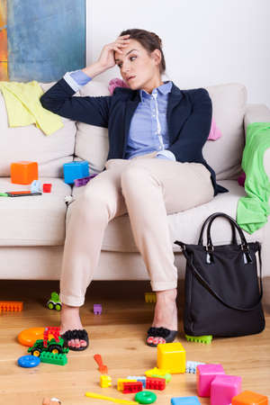 Tired young mother sitting on sofa after hard day at work