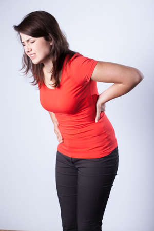 sacral spine: Young pretty woman and pain in the back Stock Photo