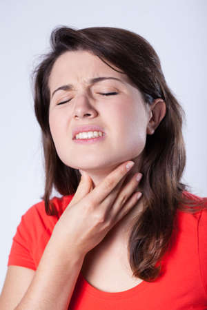 Young ill woman and terrible sore throat photo